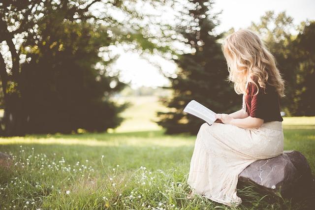 Een vrouw met lang blond haar zit dromerig te lezen in een weidse tuin. Wat houdt een hypnose sessie in? Geboeid lezen is een vorm van hypnose.